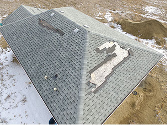 High Definition Image of a residential roof inspection of wind damage to the asphalt shingles of a cottage style roof.